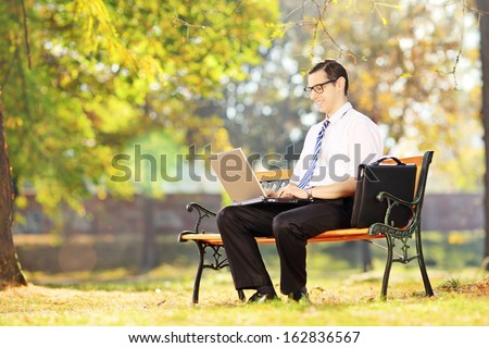 Young smiling businessperson sitting on a wooden bench and working on a laptop in a park - stock photo
