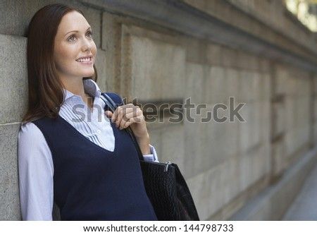 Young smiling businesswoman leaning against wall in street - stock photo