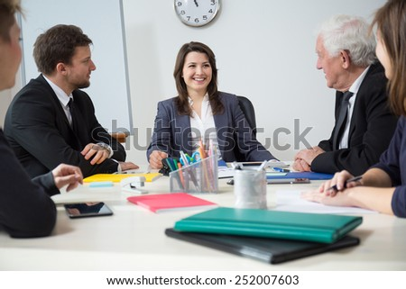 Young smiling businesswoman on funny business meeting - stock photo