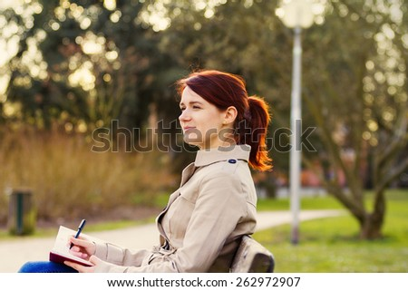 Young smiling businesswoman sitting in a classic city park,student professional outdoors  holding a red ,journal writing in it.Businesswoman smiling,Life style, - stock photo