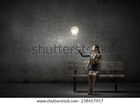 Young smiling businesswoman sitting on bench with book on knees - stock photo