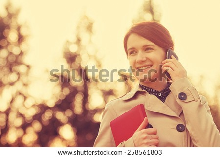 Young smiling businesswoman,student professional outdoors talking on cell smart phone and  holding a red journal.Businesswoman smiling,Life style, - stock photo