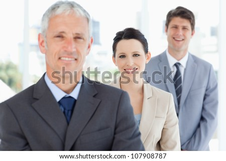Young smiling businesswoman wearing a formal suit between two executives - stock photo