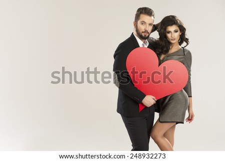 young smiling caucasian couple holding sign in form of red heart   - stock photo