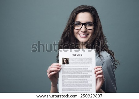 Young smiling cheerful woman holding her resume - stock photo