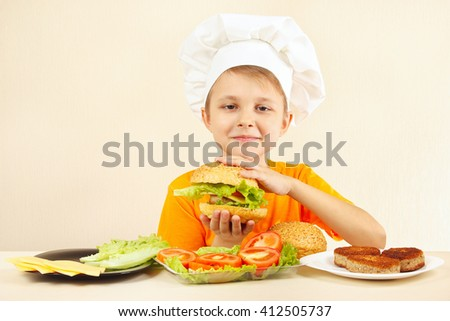 Young smiling chef in chefs hat enjoys a cooking tasty hamburger - stock photo