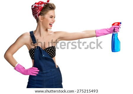 Young smiling cleaner woman wearing pink rubber protective gloves holding blue spray bottle / young beautiful American pin-up girl isolated on white background. Cleaning service concept - stock photo