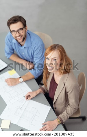 Young Smiling Co-Workers Looking Up at Camera While Discussing Paperwork in Business Meeting - stock photo