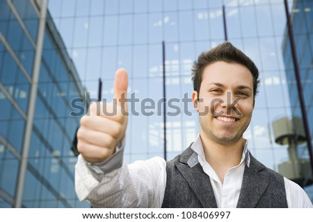 Young smiling confident man doing thumbs up sign outside contemporary office building. Focus on face. Shallow DOF. - stock photo