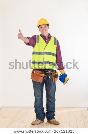 Young smiling construction worker in the house currently under renovation - stock photo