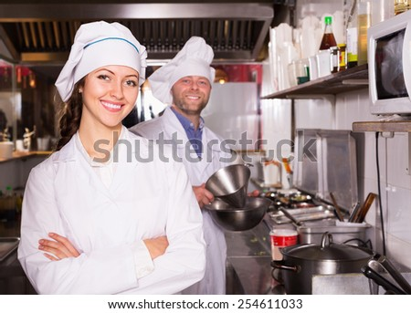 Young smiling cooks greeting customers at bistro kitchen - stock photo