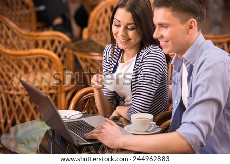 Young smiling couple are using laptop at cafe. - stock photo