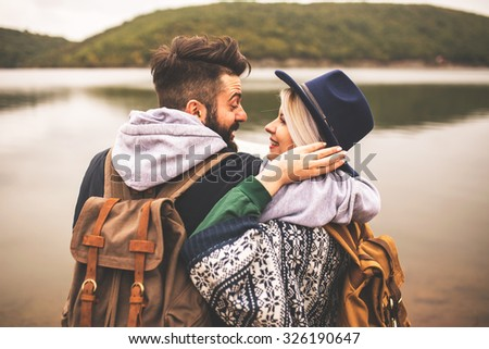 Young smiling couple enjoying nature and their hiking together  - stock photo