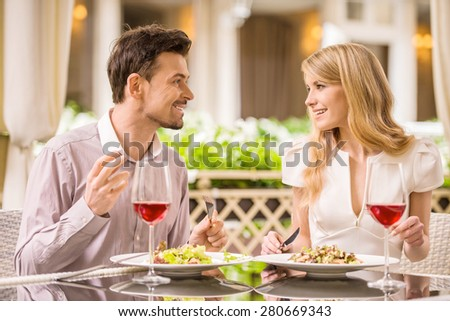 Young smiling couple enjoying the meal in gorgeous restaurant. - stock photo