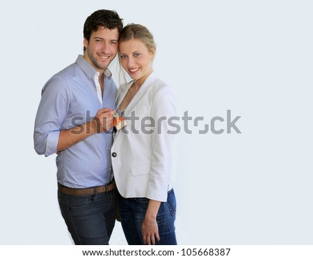Young smiling couple holding keys of their new house - stock photo