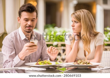 Young smiling couple in gorgeous restaurant. Man looking at phone. - stock photo