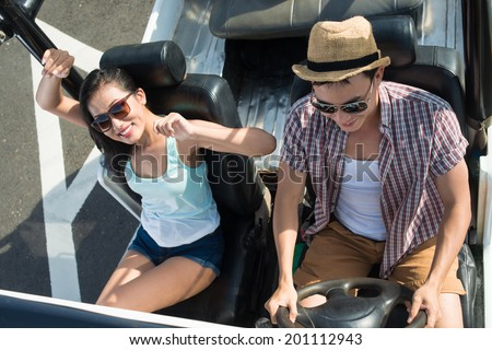 Young smiling couple in sunglasses travelling by off-road vehicle, view from above - stock photo