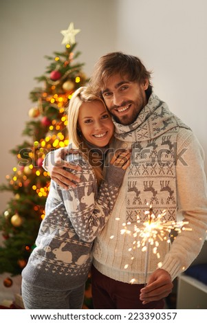 Young smiling couple looking at camera on Christmas night - stock photo