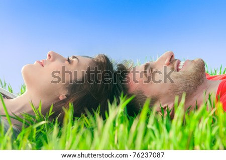 Young smiling couple lying down on the grass and dreaming at their future - stock photo
