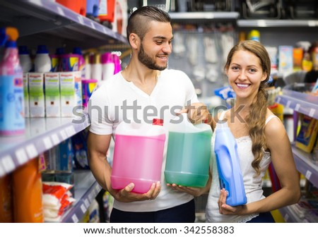Young smiling couple selecting detergents at the household store - stock photo