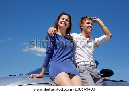 Young smiling couple stands leaning on car on background of blue sky - stock photo