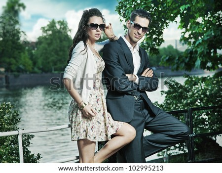 Young, smiling couple wearing sunglasses - stock photo