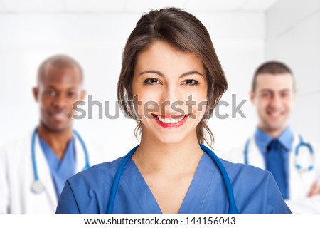 Young smiling doctor in front of her team - stock photo