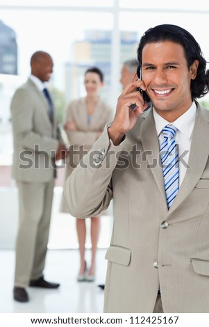 Young smiling executive talking on the phone and with his team behind him - stock photo