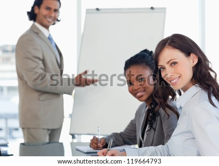 Young smiling executives sitting at the desk with a co-worker behind them - stock photo