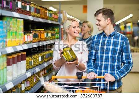 Young smiling family purchasing canned food for week at supermarket - stock photo