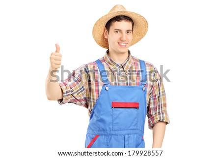 Young smiling farmer giving a thumb up isolated on white background - stock photo
