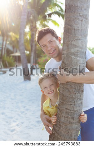 young smiling father and his adorable son playing and having fun together at the beach - stock photo
