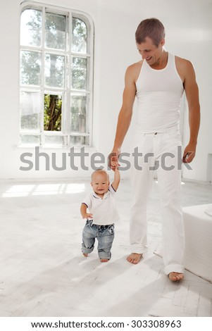 Young smiling father with his nine months old son learning to walk at home on white home background - stock photo