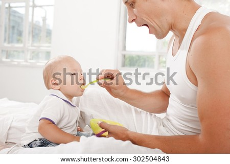 Young smiling father with his nine months old son on the bed at home on white home background. Dad feeding his son with a spoon - stock photo