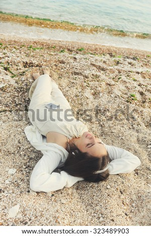 Young smiling female dressed in white clothing lying on a sea sand and listening music. - stock photo