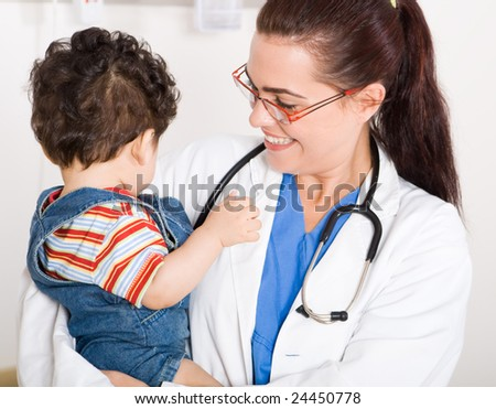 young smiling female pediatrician holding a cute baby boy - stock photo