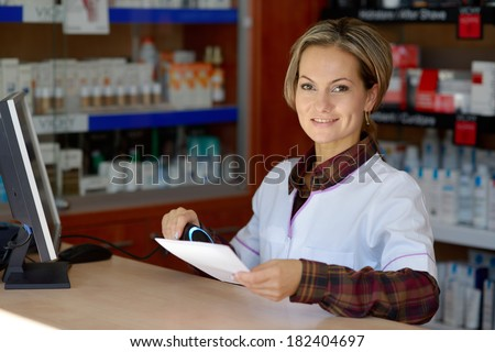 young smiling female pharmacist holding prescription - stock photo