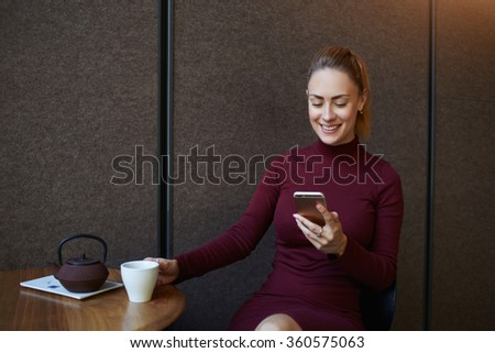 Young smiling female reading text message on mobile phone while resting in coffee shop interior, attractive woman watching funny video on cell telephone while enjoying cup of tea in modern restaurant  - stock photo