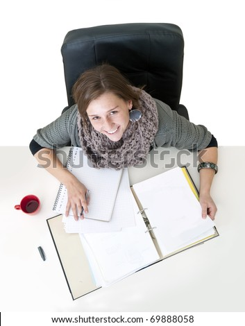 Young smiling female student looking up from the notes on her desk seen from above - stock photo