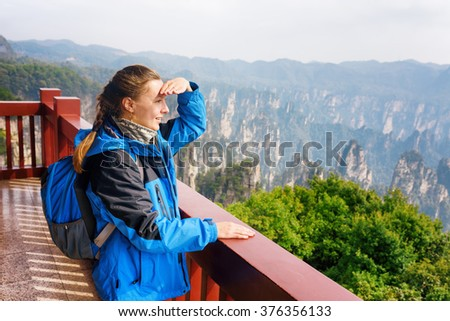 Young smiling female tourist with blue backpack enjoying beautiful mountain view in the Zhangjiajie National Forest Park, Hunan Province, China. Her hair braided in French plait. Outdoor portrait. - stock photo