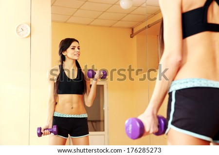 Young smiling fit woman doing exercises with dumbells and looking at her reflection at gym - stock photo