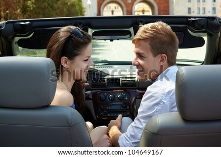 Young smiling girl and a guy sit in the car, standing against building with two arches, and look at each other, back view - stock photo