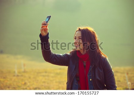 young smiling girl in casual clothes take photo with mobile phone outdoor shot  - stock photo