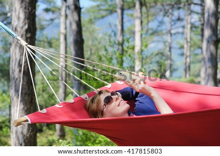 Young smiling girl in glasses enjoy on red hammock in forest. Redhead woman with freckles  smiles, talking on smartphone. Forest, mountains in the background. - stock photo