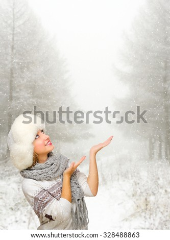 Young smiling girl shows pointing gesture at snowy forest - stock photo
