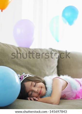 Young smiling girl sleeping on sofa with balloons - stock photo