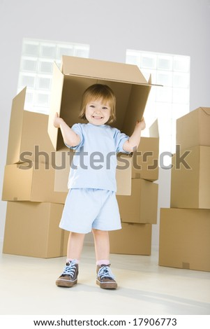 Young smiling girl standing between cadboard boxes. She's holding one box over head. She's looking at camera. - stock photo