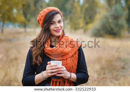 Young smiling girl with a cup of coffee (tea) for a walk in the park outdoors. Autumn weather. - stock photo