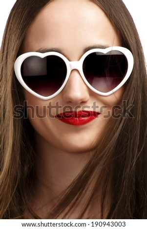 Young smiling girl with heart-shaped glasses, isolated on white - stock photo