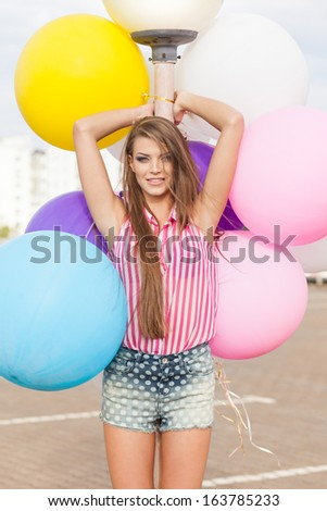 young smiling girl with messy hair in short denim shorts and sleeveless striped top leans on light-pole holding bunch of bright balloons - stock photo